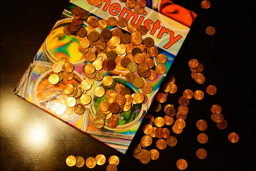 Photo+illustration+of+a+textbook+covered+in+coins