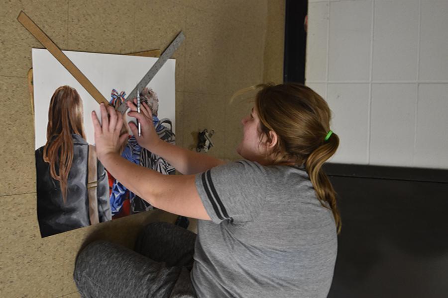 Working on hands and knees, senior Sierra Garner works on a composition.
