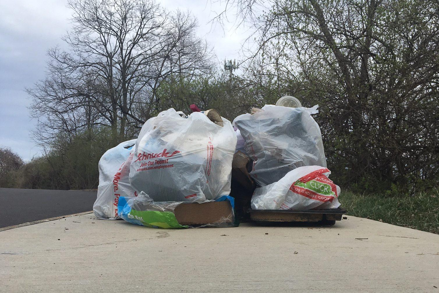 Bags of trash pile up as the road connecting the middle and high school is cleared of litter.