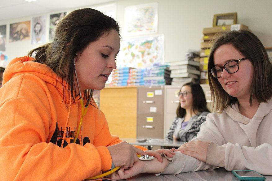 Sophomore Emily Sexton uses a stethoscope to measure sophomore Clair Osterhaus's heart beat.