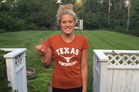 Putting up the Texas Longhorns hand sign, senior Evie Pfeifer poses for her commitment to University of Texas at Austin.