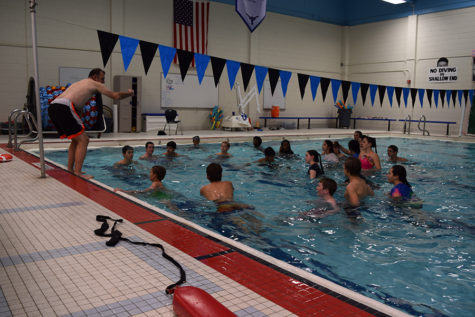 Teacher Tim Corteville instructs his primarily freshman P.E. class from the side of the pool as a part of the swim unit.