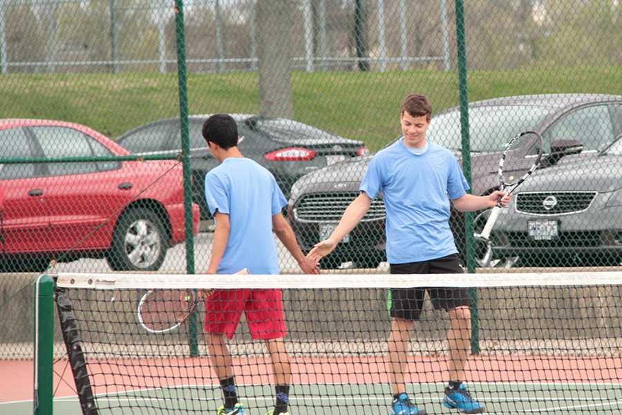 After winning a point, seniors Dillon Youngberg and Kenji Yanaba encourage each other as double partners.