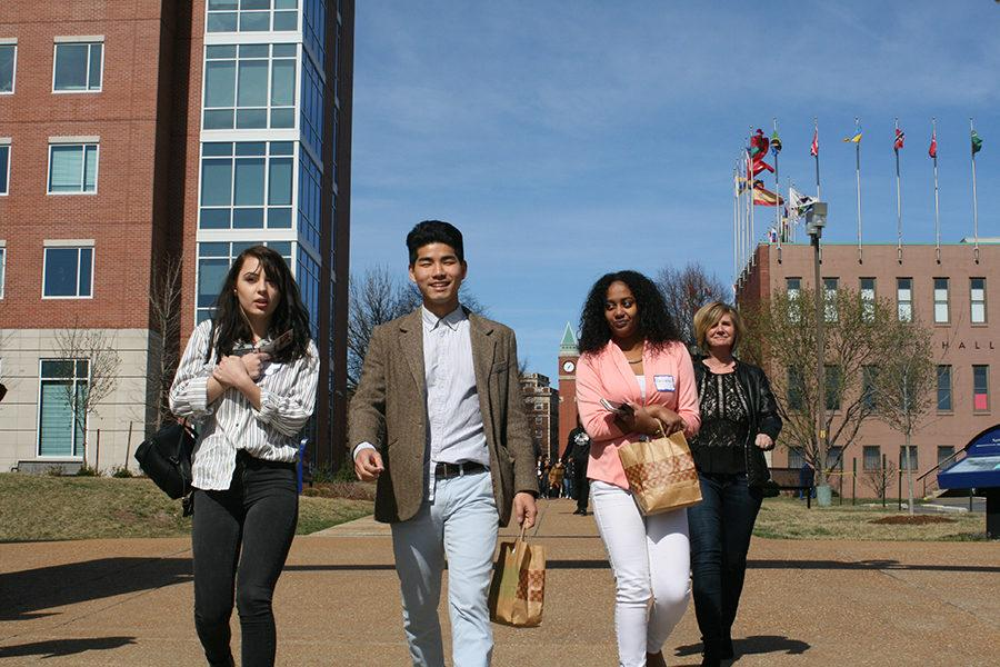"""Sophomore Allani Gordon, junior Joon Bang, senior Bersabeh Mesfin and sophomore principal Jen Sebold walk to the third summit, held in SLU's cultural center. At that summit, they presented their diversity solutions to Edward Jones. """"Every lesson we were taught, every project we did, I want to take that with me in my life and my journey and discover things about myself and how I can do good for the community and the world,"""" Mesfin said."""
