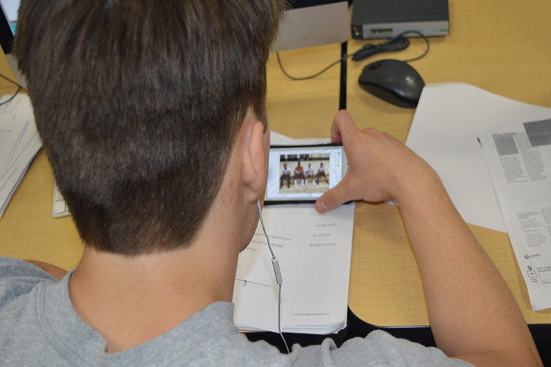 With headphones in, student watches a YouTube video in class. A study by the University of Nebraska estimates that students spend up to 20 percent of class time on phones.