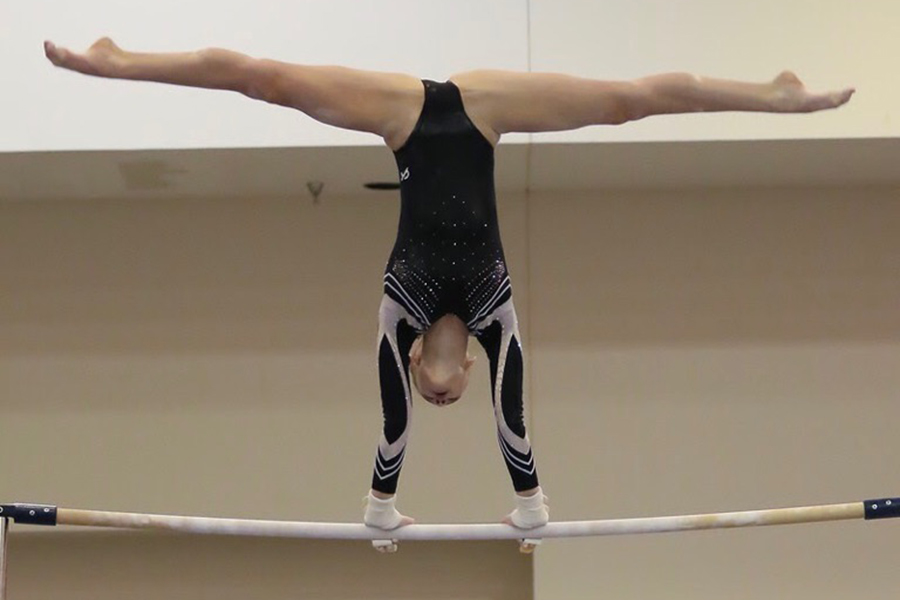 Sophomore Abby Socha does a cast handstand on bars at the World Class meet.