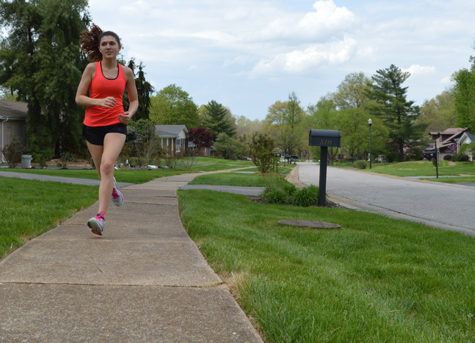 Running down the street, freshman Emma Caplinger trains for upcoming cross country summer camps.