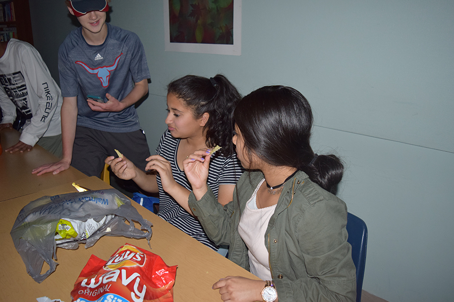 Freshmen Rabiah Hilaly and Umeera Farooq start a food party in class despite the power outage.