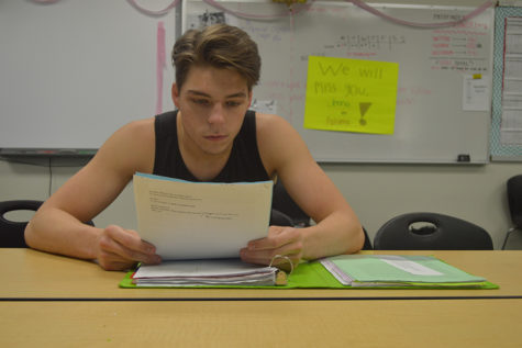 Using his Physics review guide, senior Brandon Eckhoff solves force problems.