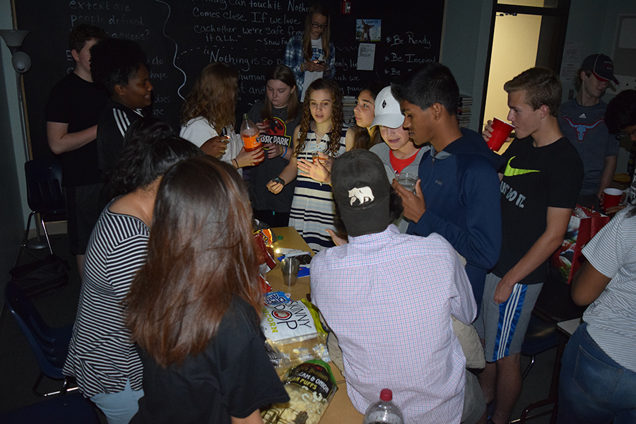 Students crowd around a table full of food as an end of the year reward.
