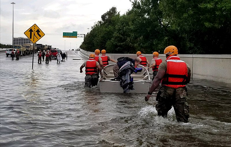 The Texas Army National Guard pulls a boat across a flooded highway in Houston.