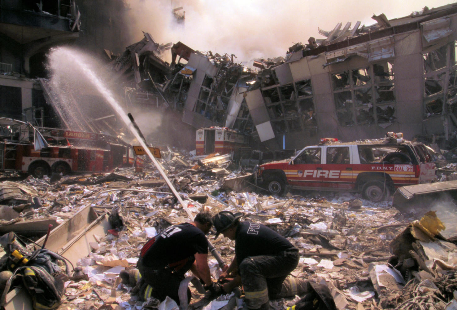 Firefighters+douse+flames+and+search+for+survivors+in+the+rubble+of+the+Twin+Towers+in+the+aftermath+of+the+Sept.+11+attacks.