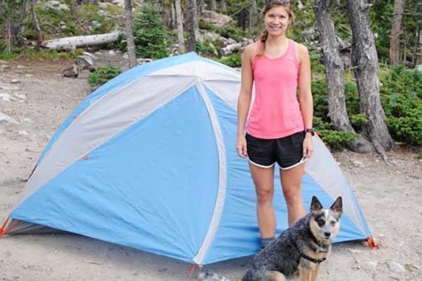 Standing by a tent while camping, math teacher Michelle Meers poses by her dog, Meeko.