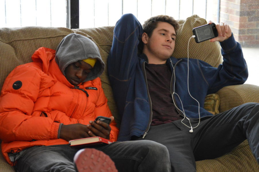"""Playing on their phones instead of doing homework, seniors Terrell Jones and Jonathan Dixon relax in the senior lounge. The senior lounge was given to seniors as an alternative to the study hall rooms, but Dixon used it as a place to watch Netflix. """"The moment I stepped into West High this year I knew I wanted to get out as soon as possible,"""" Dixon said."""