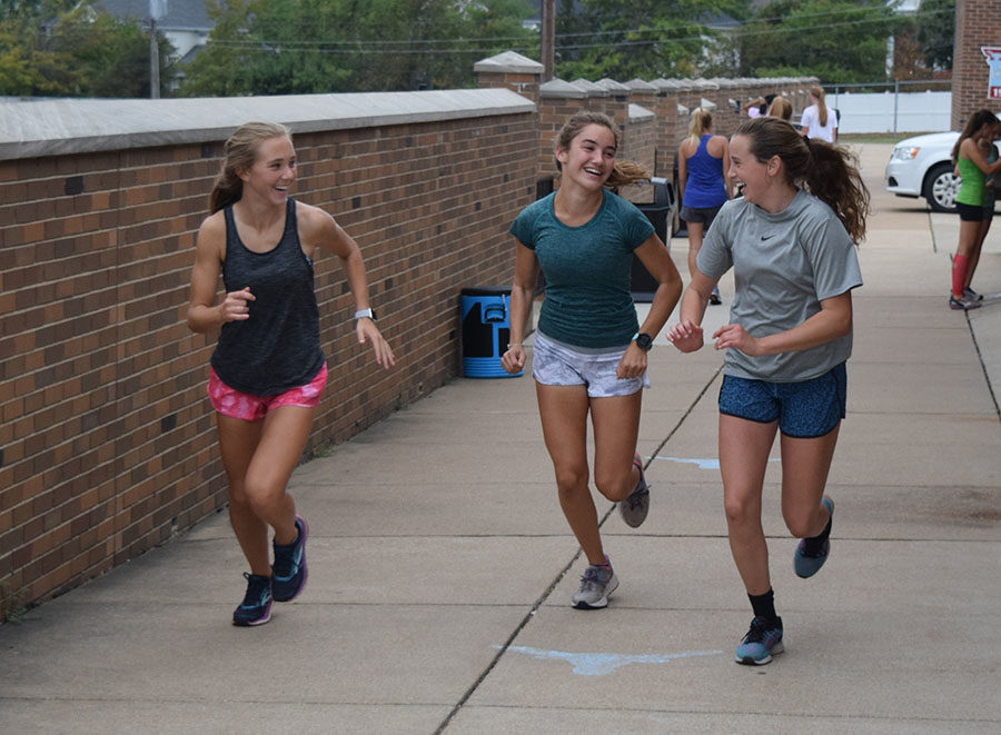 Laughing, freshman Leah Selm, sophomore Chloe Hershenow and freshman Anna Butler start out on an easy road run.