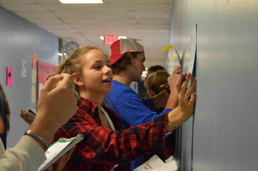 Senior Ava Brao completes a College Algebra workstation activity in the math hallway.