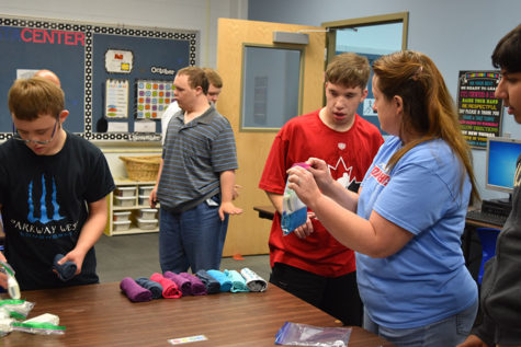 Special School District teacher Therese Meres helps senior Nick Waldrop package a hygiene kit. Over 100 shoe boxes were filled by West students.
