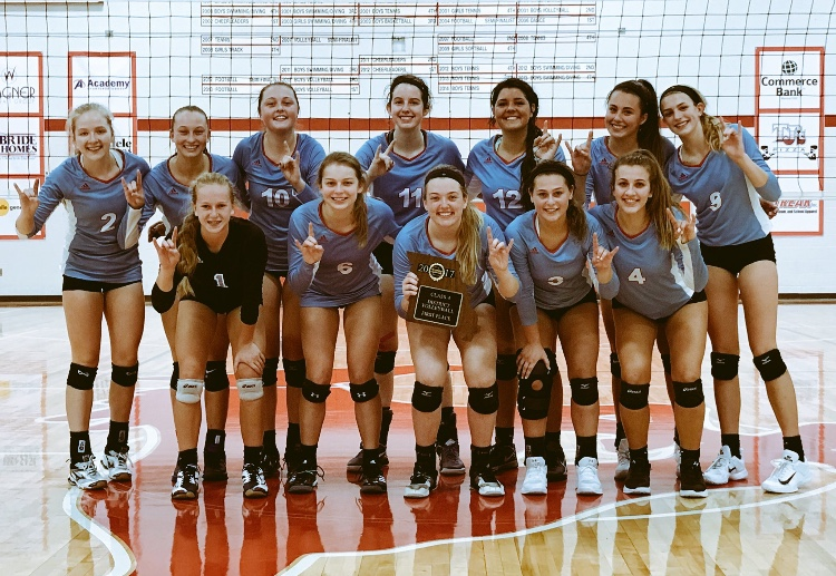 Posing+with+their+first+place+plaque%2C+the+varsity+girls+volleyball+team+make+longhorn+symbols+with+their+hands.+