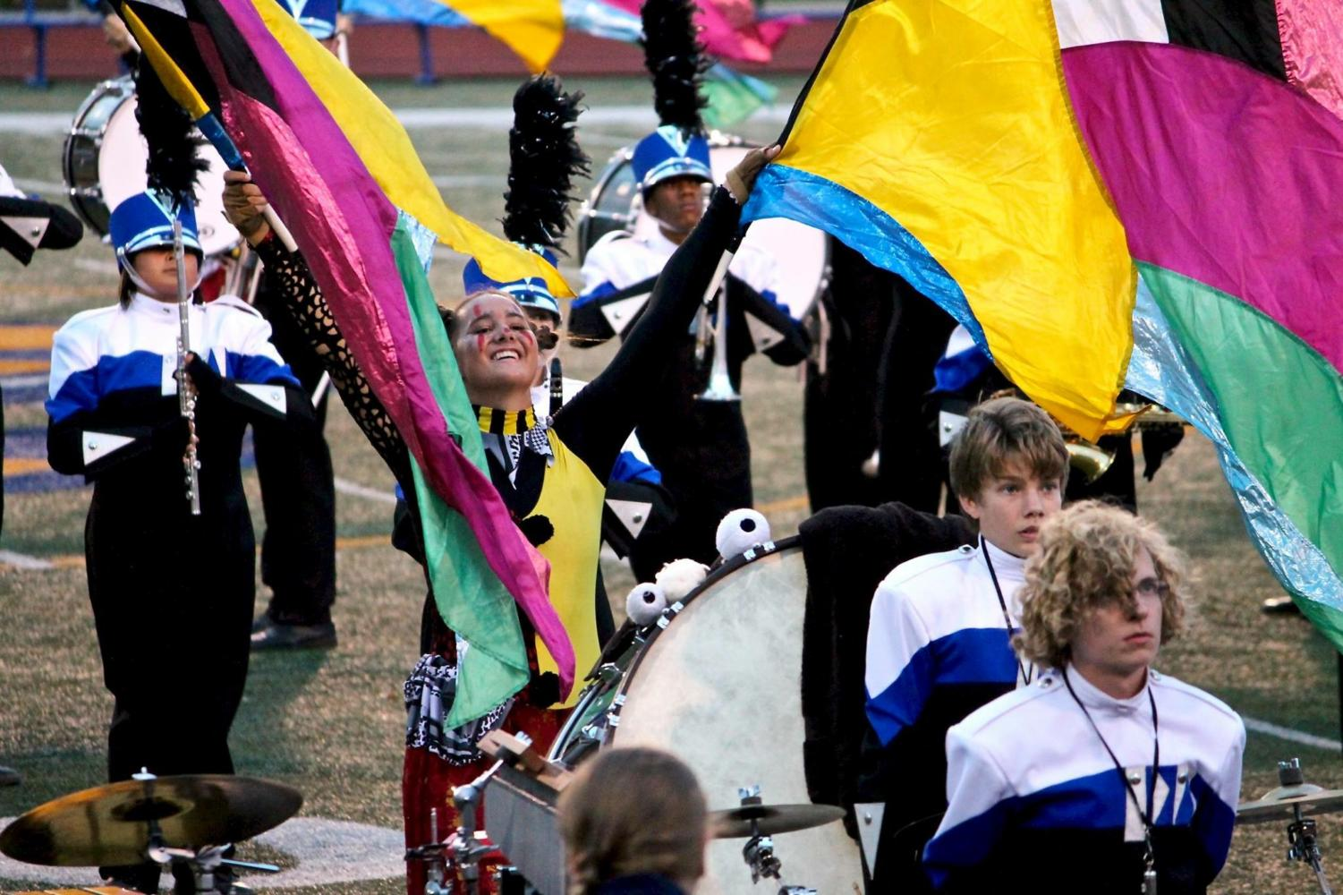 "Senior Noelle McGuire waves her color guard flags in the air at the Jaguar Pride Marching invitational. The competition was the marching band's last, and took place this Saturday. Color guard walked away having been awarded ""Best Auxiliary,"" which has not happened in a long time."