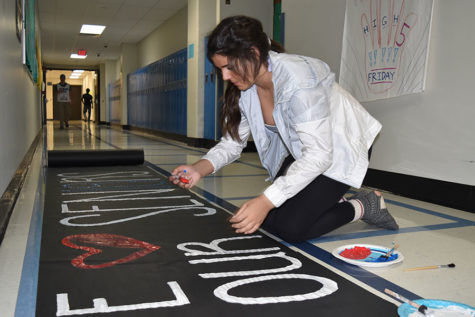 "Senior Caroline Shaw paints a banner for the senior team for the powder puff game. She views the game as a fun memory and community-building experience. ""I was super excited [to play] and I honestly signed up the first day that forms got handed out,"" Shaw said."