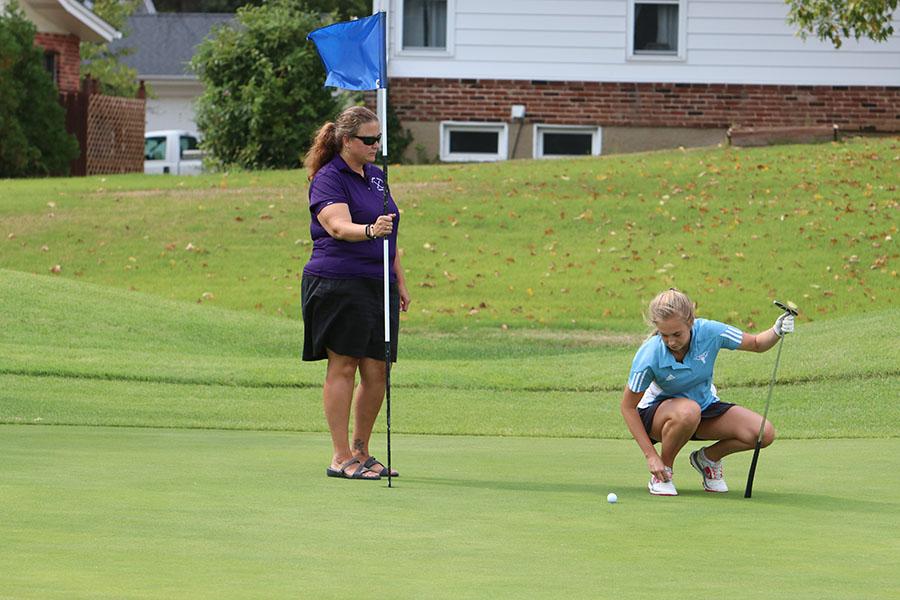 Lining up her putt, senior Kacie Bergh prepares a shot during a varsity match.