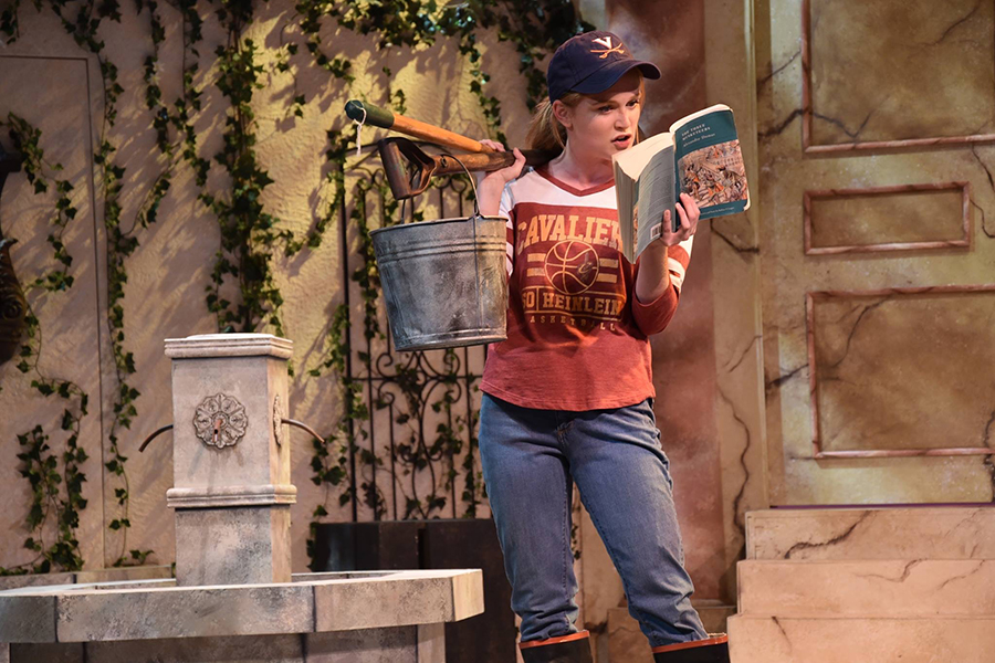 """Reading a book to the audience, Kathryn Harter leads a scene in """"The Three Musketeers"""" as Sabine in June 2017."""