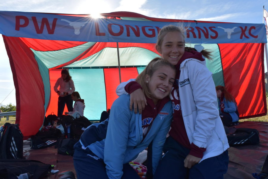 With light shining through the team's red and blue tent, freshman Leah Selm and senior Hannah Roth huddle up on a chilly morning at the West Invitational.