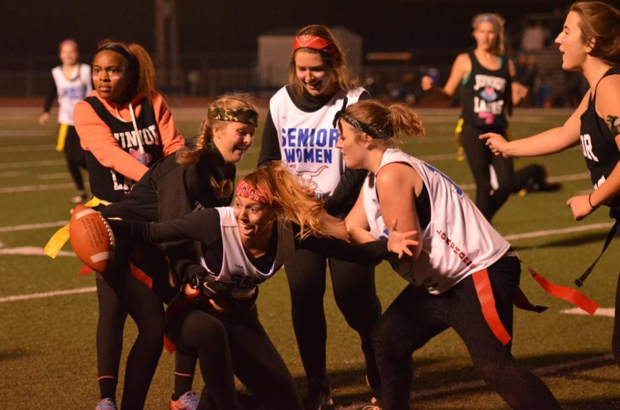Running from the juniors, senior Emma Moss tries to prevent her flag from being pulled. Moss tried to score a touchdown during the annual Powder Puff game.