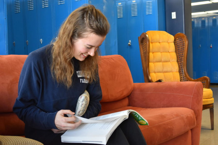 """With plenty of makeup work to do after her week of recovery, Senior Kaleigh Stanfield looks through her AP Psychology review book and holds the pillow she was given by the hospital after surgery to her rib. """"The pillow helps to compress the area where the rib was taken out,"""" Stanfield said."""