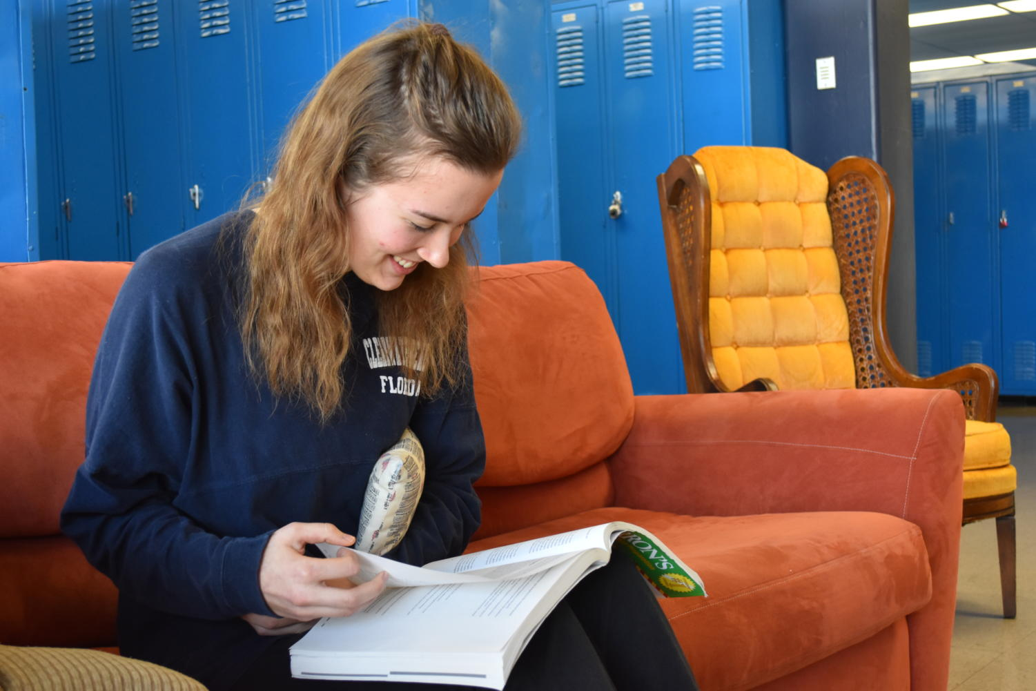 "With plenty of makeup work to do after her week of recovery, Senior Kaleigh Stanfield looks through her AP Psychology review book and holds the pillow she was given by the hospital after surgery to her rib. ""The pillow helps to compress the area where the rib was taken out,"" Stanfield said."