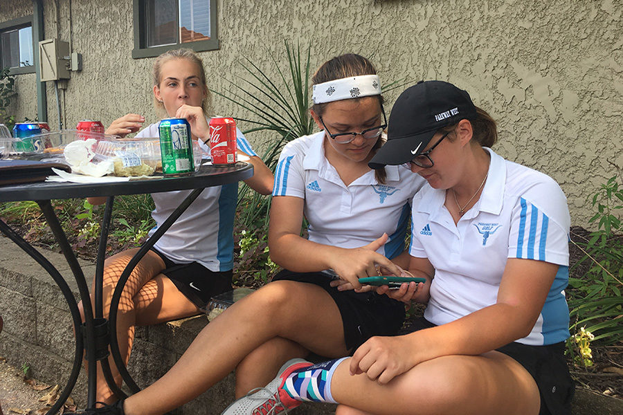 """Senior Kacie Bergh and juniors Ashley Spillman and Clair Osterhaus sit and eat lunch after their conference match at Crescent Farms. """"After conference, I could only think about how good the food was,"""" Osterhaus said. """"Contrary to popular belief, it's really hard walking 18 holes of golf, so I was really proud of the team. It's hard playing for five hours straight, so getting to eat after is fantastic."""""""