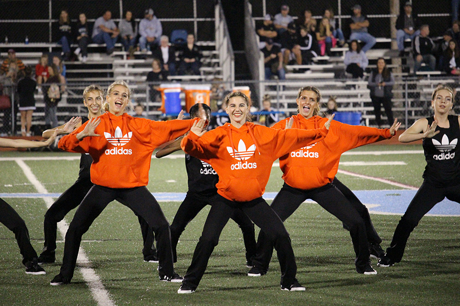 Freshman Emma Roth dances in black Adidas-wear behind varsity in orange at the homecoming game. Roth performed a back handspring during the dance.