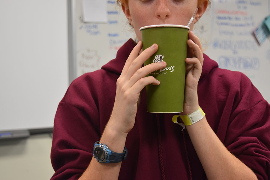 A student drinks coffee during school. Students currently bring coffee to school from places like Starbucks, Panera, and 6 North.