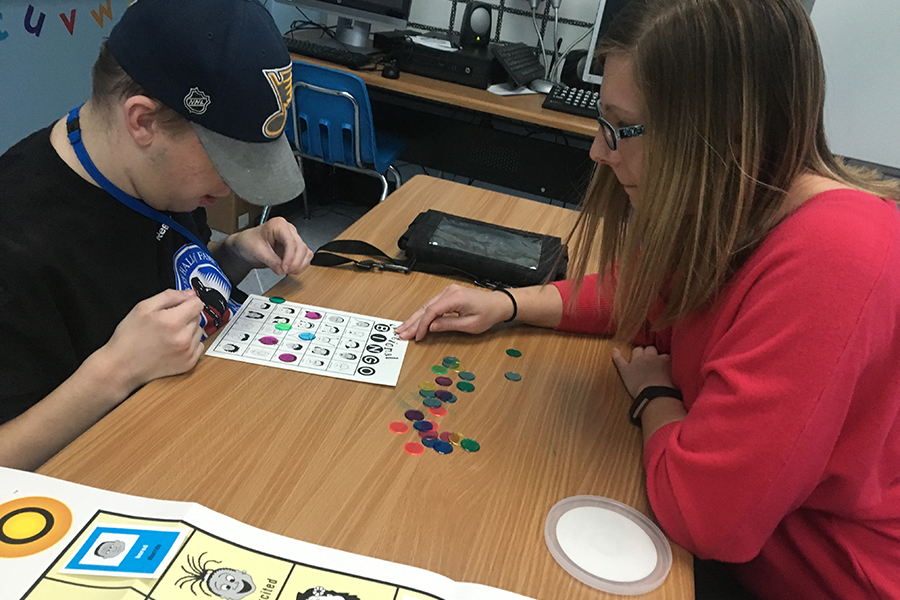 """Special Education teacher Nicole Sneed helps senior Nicholas Waldrop at a game of bingo. """"My favorite thing about my job is the relationship I have with my students. I enjoy having inside jokes with my students as well as knowing their interests. It helps us connect and form a positive relationship,"""