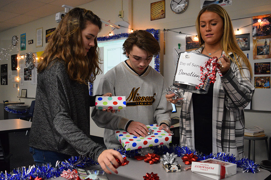 Wrapping gifts and organizing supplies, sophomore Rachel Deadwyler, junior Johnathan Stephens and senior Brandi Beaubien set up for Marketing II's holiday wrapping event. Community members have the opportunity to bring the gifts for marketing and DECA students to wrap in exchange for a donation to the Day of Service programming.