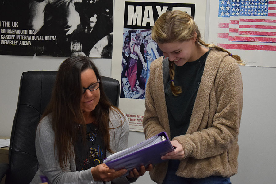 """Helping sophomore Kelsey Long with an assignment, social studies teacher Kristen Collins reads Long's response on a review packet. Long enrolled in World History because it was a very engaging class. """"Collins was one of the best teachers I've ever had, because she helped organize us and she worked overtime to be sure we were successful,"""" Long said."""