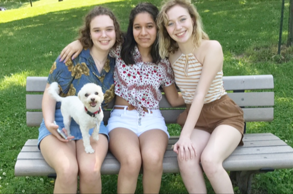"Enjoying the summer day, maltipoo Ruby smiles with juniors Juliane Pautrot, Megan Roberts and Kristin Priest. Roberts made an Instagram account dedicated to posting selfies of her dog. ""Ruby's very feisty and sassy, she has such an attitude,"" Roberts said. ""Ruby literally thrives off of socializing."""