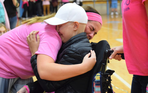 Receiving her honorary high school diploma with sophomore Kelly Wehrmeister by her side,  sophomore Brynn Haun smiles into an emotion-filled hug. The school held a pink-out night in Haun's honor, while students also participated in a Hamilton-themed flash mob.
