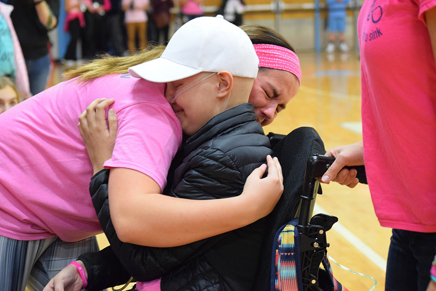 Receiving+her+honorary+high+school+diploma+with+sophomore+Kelly+Wehrmeister+by+her+side%2C++sophomore+Brynn+Haun+smiles+into+an+emotion-filled+hug.+The+school+held+a+pink-out+night+in+Haun%27s+honor%2C+while+students+also+participated+in+a+Hamilton-themed+flash+mob.+%22Brynn+meant+the+world+to+me.+She+made+me+a+better+person%2C+she+made+me+stronger+even+before+she+started+with+the+cancer+and+chemo.+She+made+me+see+a+positive+side+to+everything%2C%22+Wehrmeister+said.+%22When+she+passed%2C+she+took+a+part+of+me+with+her.+Knowing+that+she+was+such+a+huge+part+of+my+life+makes+me+sad%2C+but+also+makes+me+really+happy+to+have+had+someone+who%27s+had+that+kind+of+special+impact+on+my+life.%22