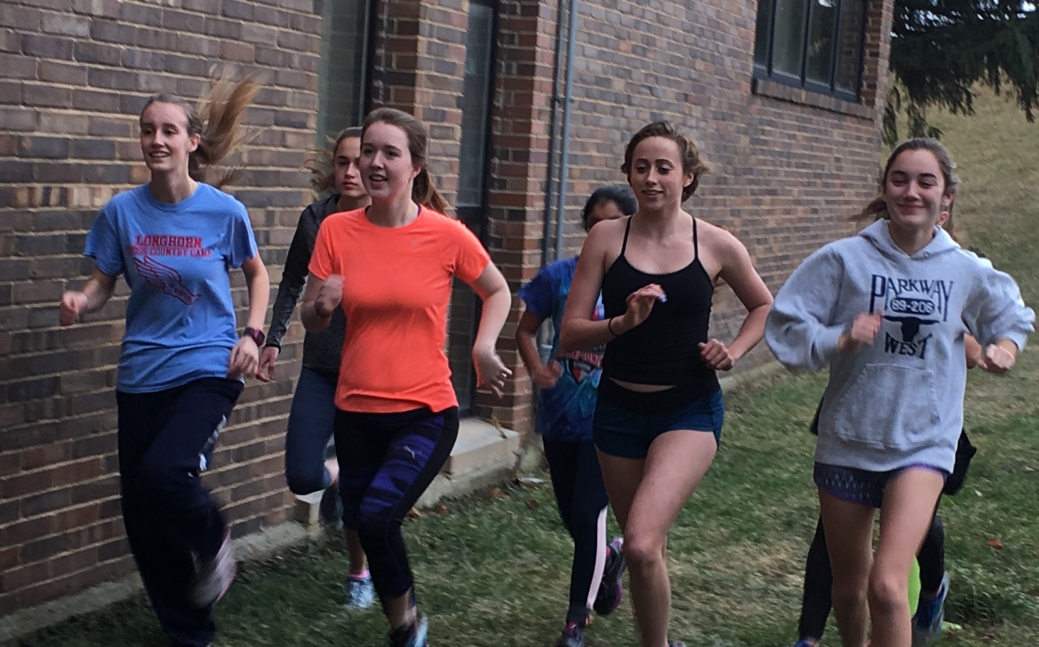"""Running their warm-up lap, sophomore Laura Rein, senior Jane Fuller, junior Natalie Butler and junior Chloe Hershenow get ready to hit the roads. After warm-up girls split into groups and completed their workout. """"Winter running helps motivate me to run on the coldest days because I know I will have these girls by my side to do it with,"""" Hershenow said."""