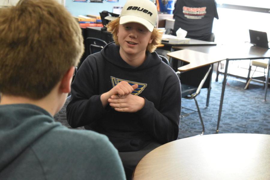 Signing to his friend, junior Andrew Aydt demonstrates ASL. Aydt began learning sign language as an infant.
