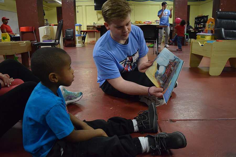 Reading+to+a+little+boy+at+Gateway+180%2C+junior+Tommy+Harper+participates+in+West%E2%80%99s+first+Day+of+Service.+Gateway+180+is+a+homeless+service+for+women%2C+children+and+families%2C+that+provides+food+and+clothes+to+those+in+need.+%E2%80%9CI+would+definitely+recommend+volunteering+with+programs+like+Gateway+180+because+it+was+really+cool.+When+we+got+there+they+showed+us+a+video+about+some+of+the+people+who+had+lived+with+them+for+awhile+and+it+was+amazing%2C+the+little+kids+were+so+nice+and+energetic%2C%E2%80%9D+Harper+said.+