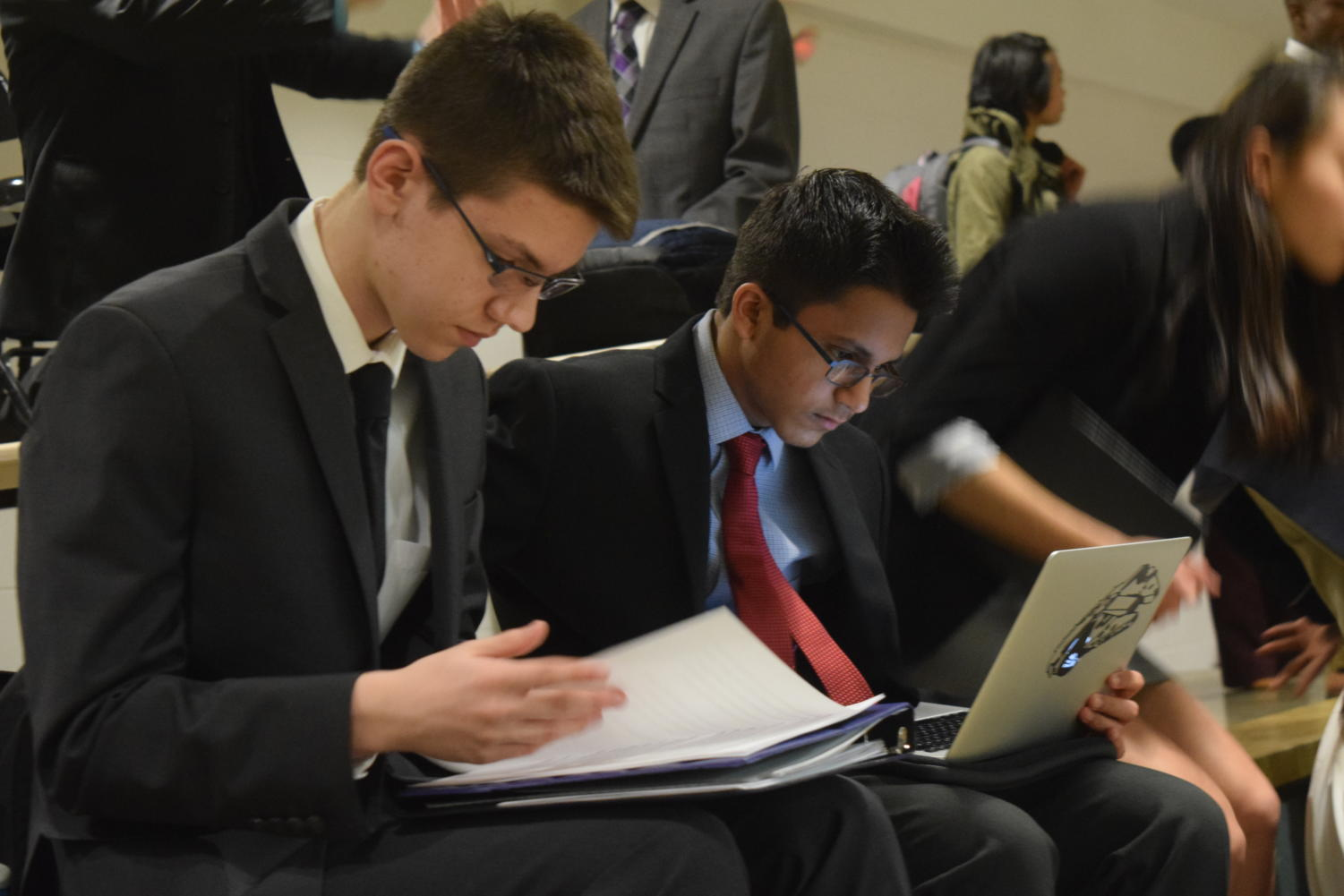 """Freshmen Tyler Kinzy and Praveen Dharmavarapu work on their cases during free time in between rounds. Jefferson City High School hosted one of the last tournaments for debate teams around the state before districts. """"I've done two tournaments so far and I've won first place at both of them, so it's definitely been something surprising, especially to join this late in the season when everyone else has been [competing] for a while,"""" Kinzy said."""