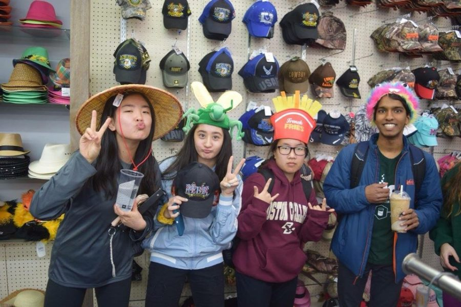 """Senior Cheryl Ma, junior Maddie Cooke and seniors Anna Chen and Haran Kumar pose with hats from Ozarkland. """"We stopped at Ozarkland and bought silly hats, and I bought a Chili's hat. Ozarkland was midwestern and had all of these funny signs,"""" Cooke said. """"One sign that we saw said 'American by birth, rebel by choice,' and that was a joke we kept saying to each other the whole time [at Jeff City]."""""""