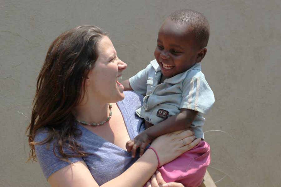 Rebecca Lintner poses with her two-year-old friend Mark, also called Markaroni, who is the son of a single mother who started the first women's empowerment group for HIV positive women.