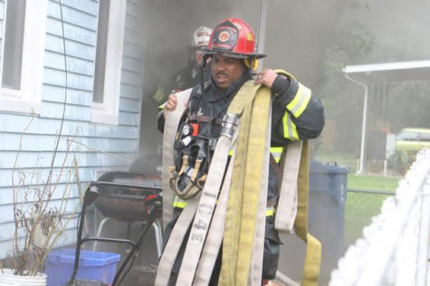 "Derrick Richardson carries a fire hose in preparation to attack a house fire. He has been a firefighter for 21 years and a Fire Captain for nine of those years. ""I hold a number of fire certifications and am able to do a multiple jobs in the fire service, Richardson said. ""I love helping people and giving back and I do that in the fire service and in my community as a volunteer. I love the job and the work it includes."""