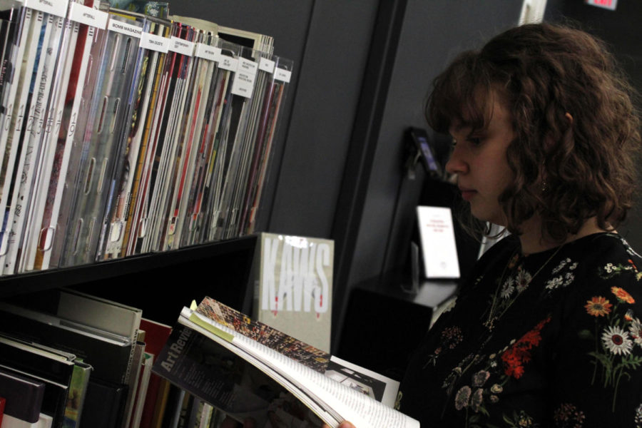 Pautrot reads from art journals and books laid out at the Contemporary Art Musuem, wearing a 60's inspired floral dress.