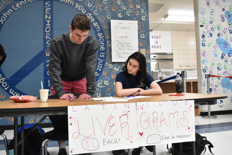 """Juniors Mitchell Norman and Natan Shrpingman sell livergrams during second lunch. The paper livers are sold for $1, and feature Latin phrases related to the holiday. """"In ancient Rome they thought love came from the liver, and so we're playing off that instead of a traditional heart,"""" Shrpingman said."""
