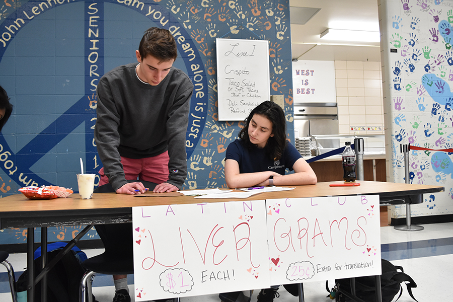 "Juniors Mitchell Norman and Natan Shrpingman sell livergrams during second lunch. The paper livers are sold for $1, and feature Latin phrases related to the holiday. ""In ancient Rome they thought love came from the liver, and so we're playing off that instead of a traditional heart,"" Shrpingman said."