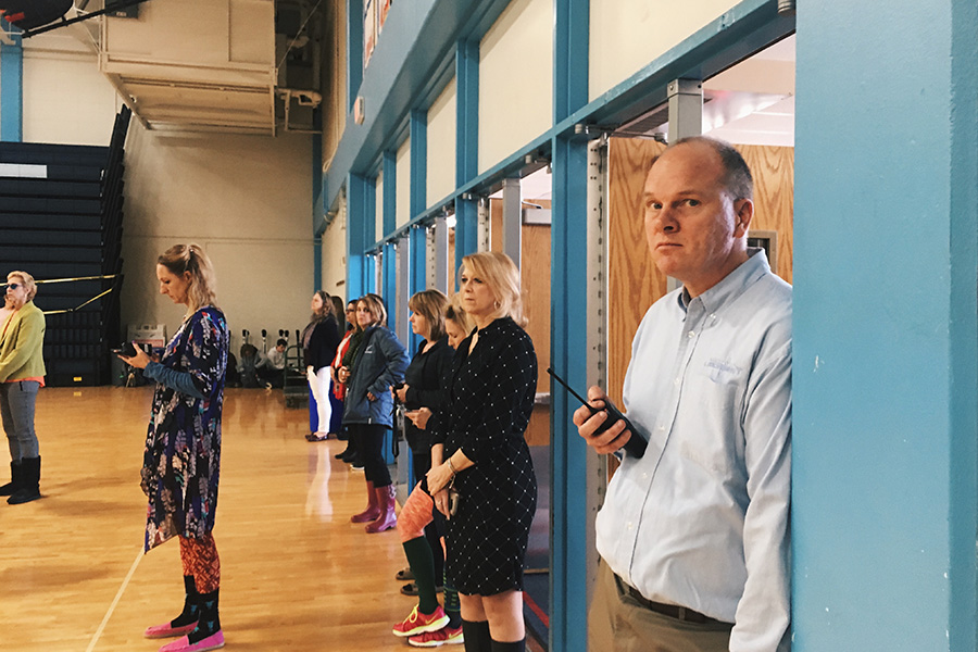 """Administrators and teachers stand at the doors of the main gym, observing the demonstration. Other Parkway schools allowed students to walk out of the building, but West students were warned of detentions when they tried to leave. """"When we tried to leave the actual building teachers told us to stop or we would get detentions, so we went out another door and stood along Clayton road, willing to face the consequences,"""" junior Maria Newton said."""